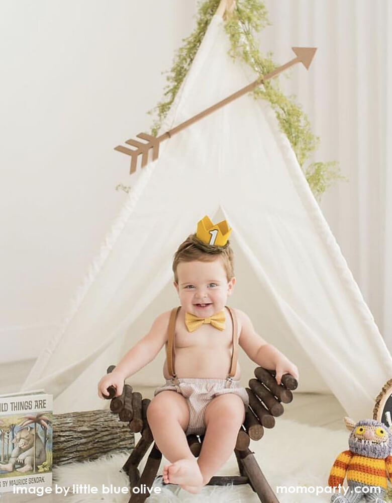"a cute Boy sitting on a wooden bench, wearing yellow tie and a adorable number one gold felt birthday crown that made with faux wolf fur, sitting in front of tant, with ""Where The Wild Things Are"" book and toy on the side, for his first wild one birthday party"