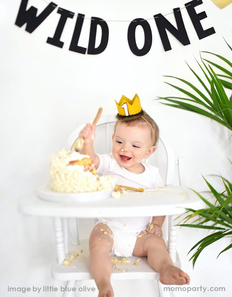 "Boy sitting on a highchair, eating his birthday cake, wearing a adorable number one gold felt birthday crown that made with faux wolf fur, a black letter ""wild one"" garland decorated on the wall, for his first wild one birthday party"