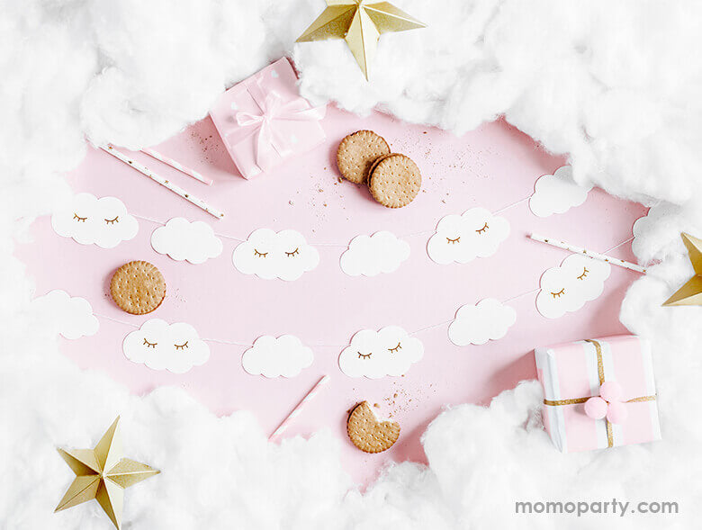 A flatlay shot of a baby pink table setup for a sweet baby girl shower filled with Little Cloud Banner , cookies, cotton around as in a cloud