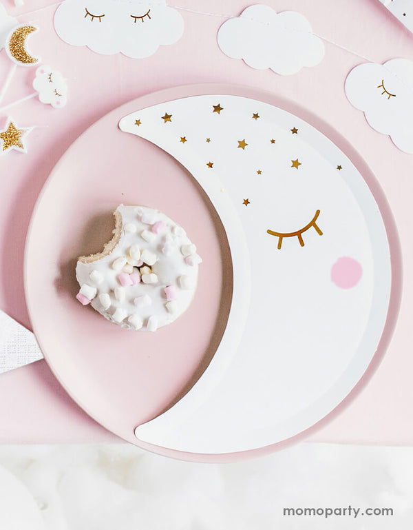 A baby shower table set up with pastel pink cover with party deco's die cut moon plates with gold foil design surrounded by cloud shaped garland