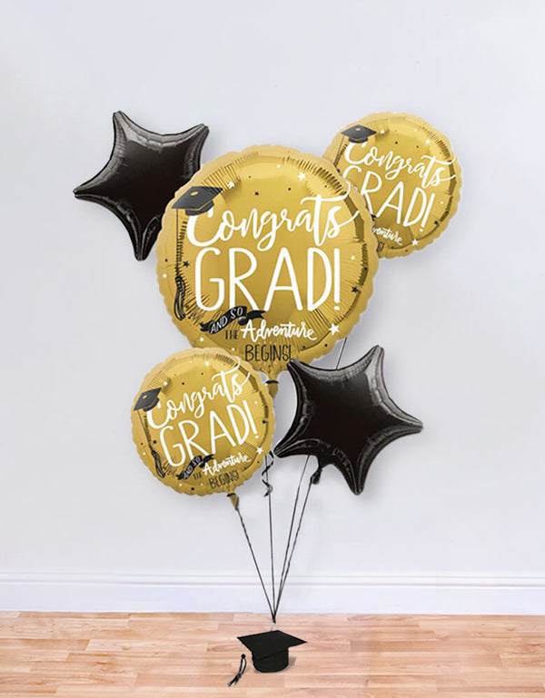 "Balloon Local Delivery of The Adventure Begins Foil Balloon Bouquet of includes a large round gold foil balloon with ""Congrats Grad!"" and ""And So The Adventure Begins"" headlines on it. Two smaller round balloons with the same design, black star balloons, ribbon, and a balloon weight for a Graduation Party and Celebration at home"