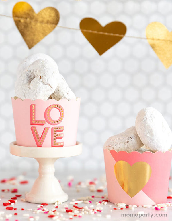 Valentine's day dessert table with mini donuts in the My Minds Eye Love Baking Cups, a gold heart garland as backdrop decoration, red pink and white sprinkler on the table