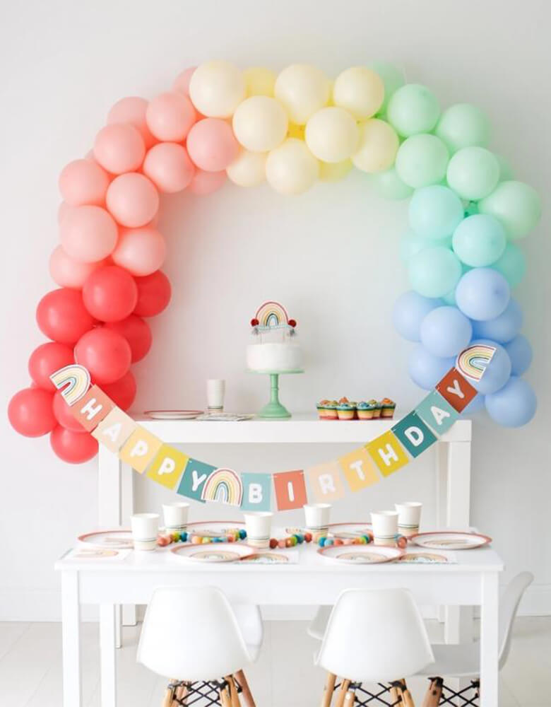 Lucy Darling Little-Rainbow-Party-in-a-Box on a party table_with a Rainbow-balloon garland as the backdrop