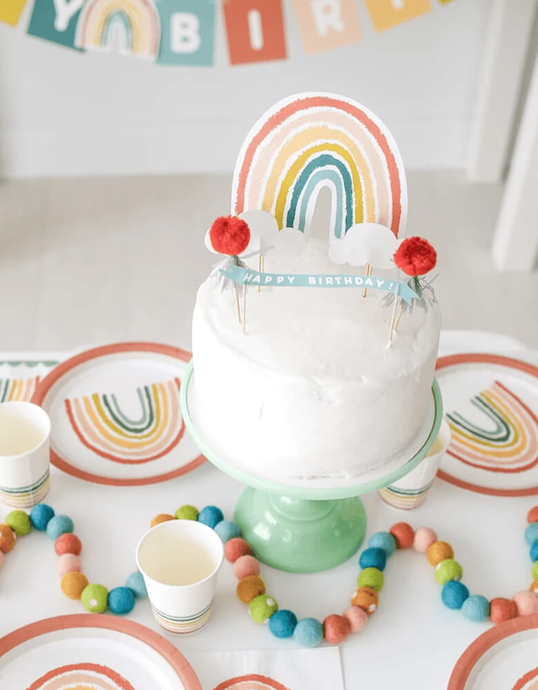 Lucy Darling Little-Rainbow-Party-in-a-Box_Rainbow-toppers-on-a cake with rainbow themed tabletops around