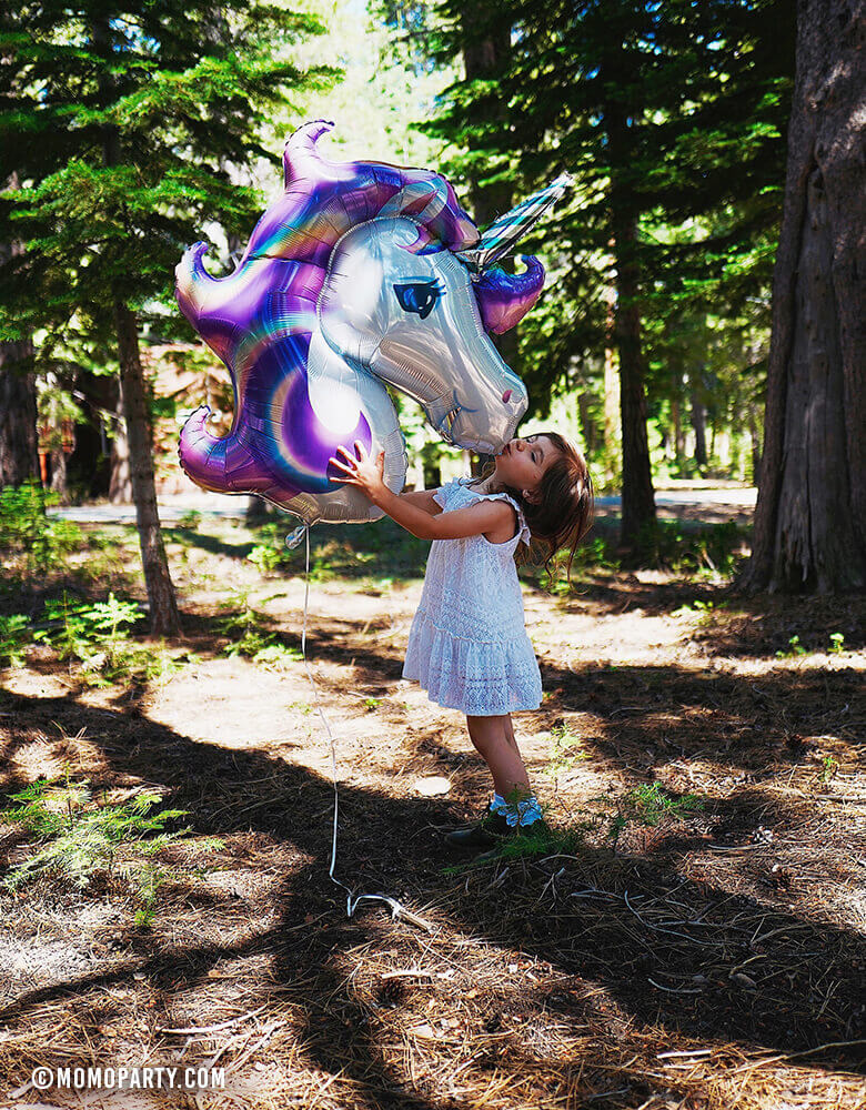 Girl kissing Giant Purple Unicorn Foil Mylar Balloon in the woods
