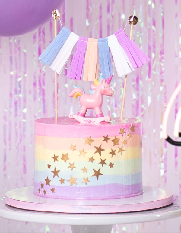 Pastel rainbow butter cream cake with unicorn toy topper and tassel topper