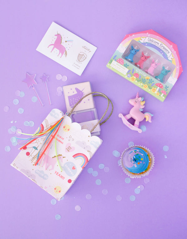 Magical Unicorn party favor bag with Day Dream Society Magical Unicorn Rubber Stamp, Unicorns & Rainbows Temporary Tattoos, Schylling Mini Unicorn Erasers, Unicorn mini wooden toy inside of Meri Meri Rainbow & Unicorn Party Bag