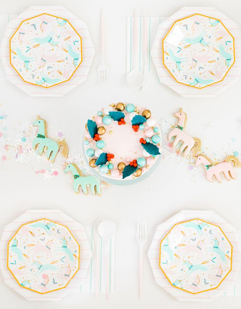 Daydream Society Magical Christmas Tableware featuring unicorn illustrations in pastel colors for a Holiday dinner party decorated with Christmas cake and matching sugar cookies