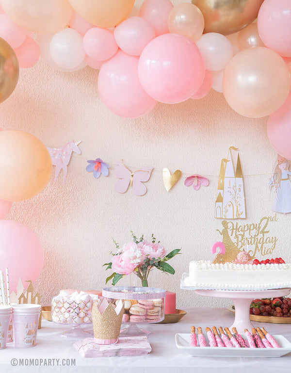 Pink and gold Modern Sweet Princess Party decoration with balloon garland, Meri Meri Magical Princess Garland , cake with customized topper, pink dessert, fruits