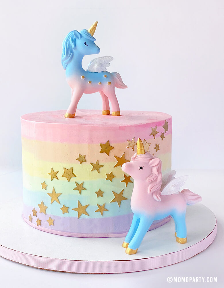 2 Magical Unicorn Cake Toppers, 4 inch tall, with blue and pink color, gold horn and gold stars on the body on a pastel rainbow star cake. Unicorn toys, Unicorn display toy for a Unicorn lover and rainbow birthday party, unicorn birthday party