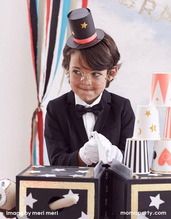 a bog dress up with a black tuxedo, wearing a Meri Meri Magician Party Hats and glasses, white glove playing a magic game in his magic themed birthday party.