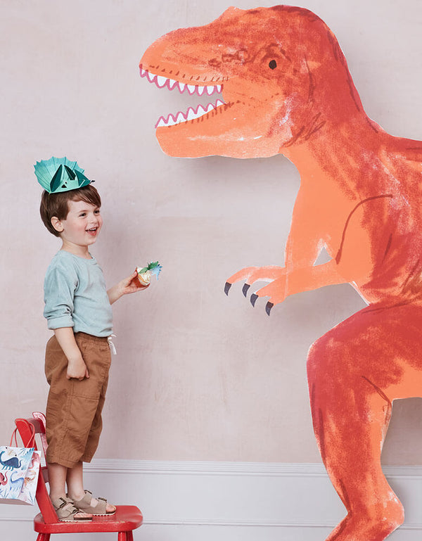 A boy in a dinosaur themed party wearing a dinosaur design hat and carries dinosaur party favor bag next to a giant t-rex cardboard standout