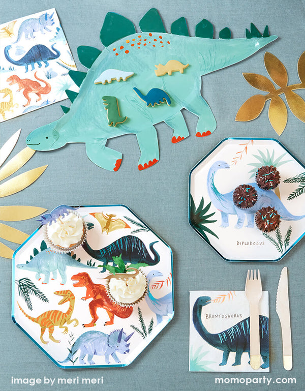 A party table for a dinosaur themed party featuring Meri Meri's Dinosaur Kingdom Colleciton inlcuding modern dinosaur plates, napkins, platter, and dinosaur cupcake toppers