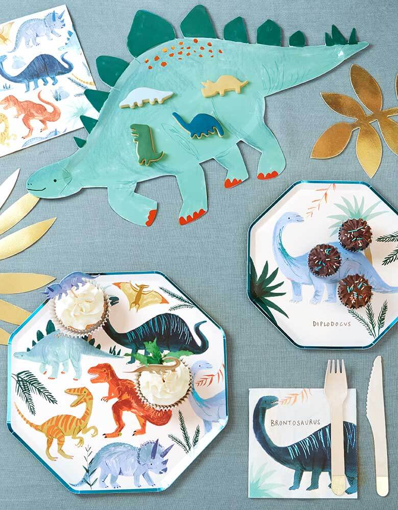 A party table for a dinosaur themed party featuring Meri Meri's Dinosaur Kingdom Colleciton inlcuding modern dinosaur plates, napkins and a Stegosaurus platter