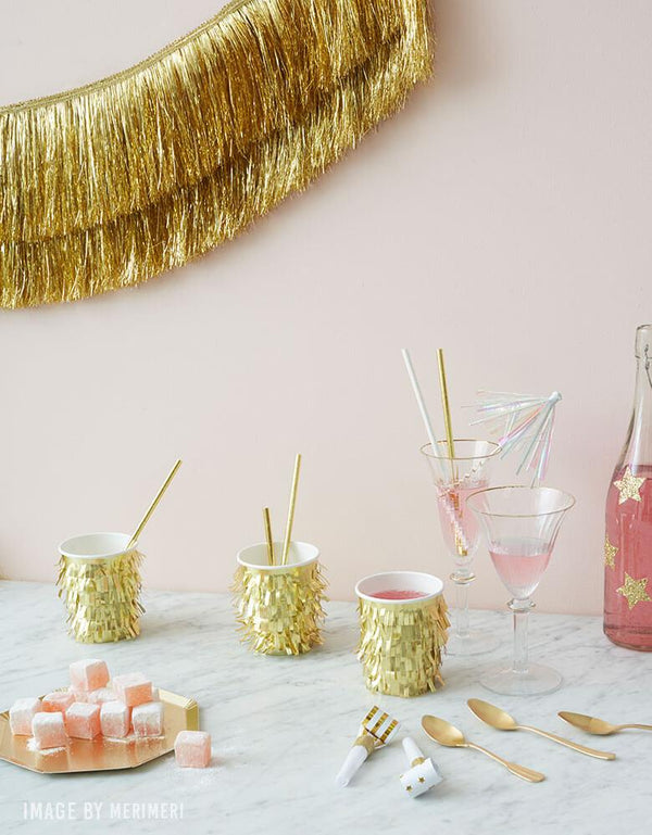 Meri-Meri-Gold-Fringe-Cups with Gold Tinsel Fringe Garland on a pale pink wall for a holiday party