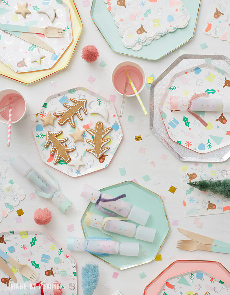 A mixture of Meri Meri's Holiday tableware featuring mint and pink dinner plates with Christmas icons design
