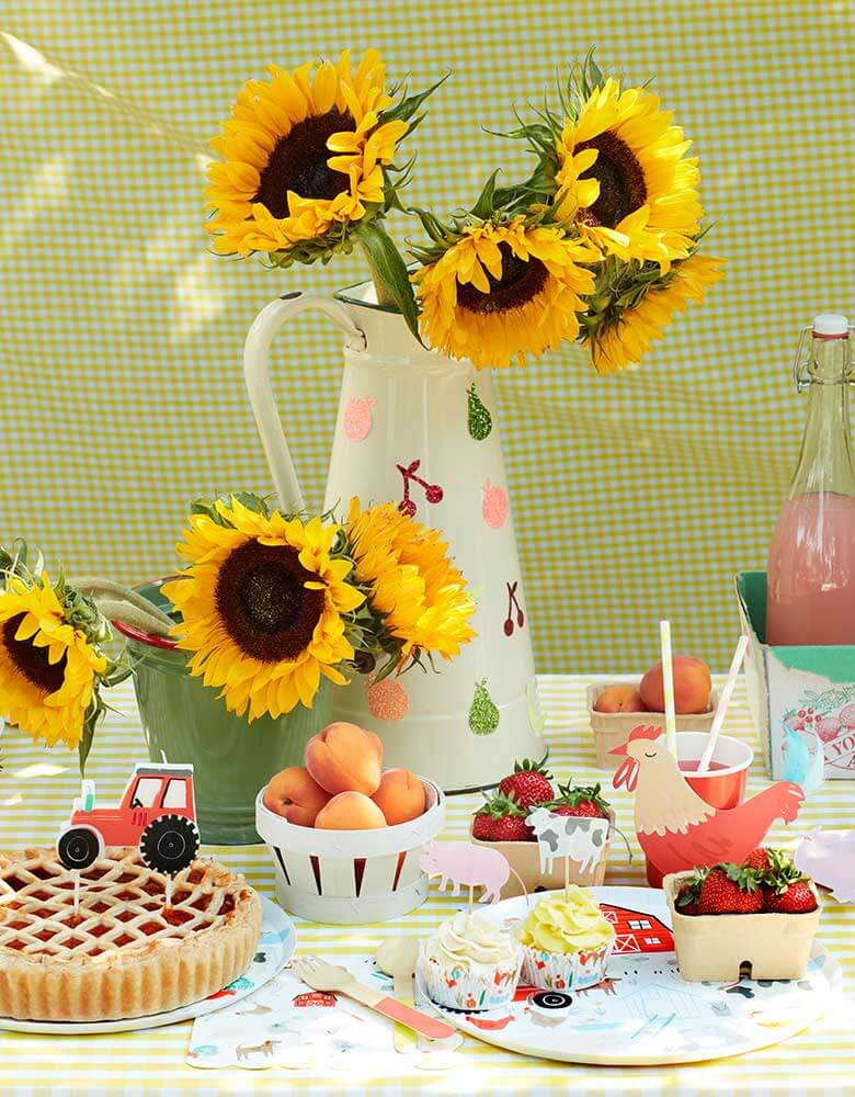 A farm themed party table with Meri-Meri's On-the-Farm-Collection_featuring farm themed party plates cups and napkins on a yellow gingham tablecloth