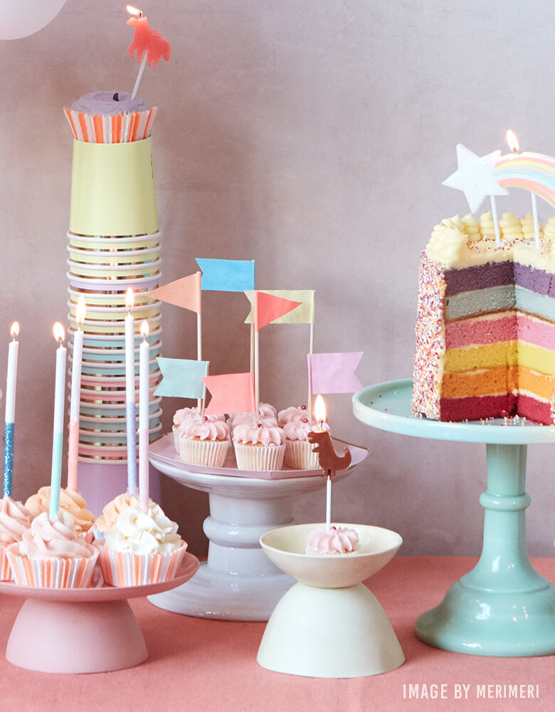 MeriMeri Cupcakes with Neon Confetti-Flag-Cupcake-Kit, Rainbow cake with Rainbow candle, pastel cups on the dessert table