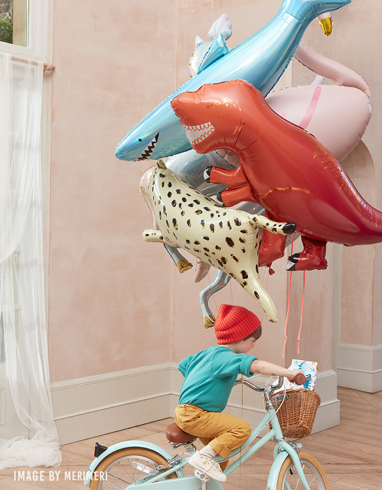 boy riding a bike with hold Meri Meri Safari Cheetah Foil Mylar Balloon, Giant Shark Balloon, Dinosaur T-rex Balloon, Circus Stallion Foil Balloon, Flamingo Mylar Balloon