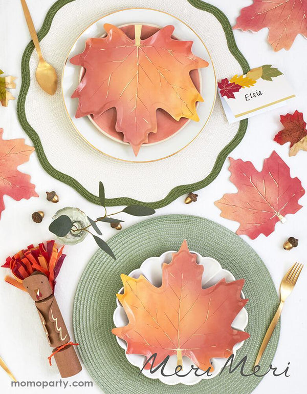 Thanksgiving dinner table with CREAM SIMPLY ECO LARGE PLATES layered with Meri Meri Maple Leaf plates, also Maple leaf Napkins on the side, They're crafted with gorgeous colors and gold foil detail. These beautiful maple leaf napkins will look sensational on your Thanksgiving celebration table