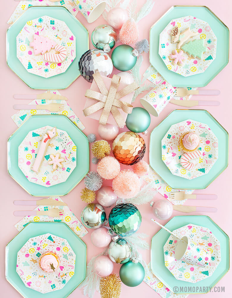 Pastel Christmas party celebration Table Set up for 6 people with Meri Meri Mint Large Dinner Plates, Daydream Society Merry and Bright Holiday Christmas Party Plates, Napkins and Cups, Pink wooden utensils and Pastel colored Sisal Trees, and Ornaments as centerpiece
