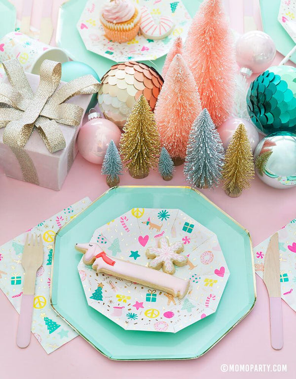 Merry and Bright Pastel Christmas table set up with cookies on top of Meri Meri Mint Large Dinner Plates and Daydream Society Merry and Bright Holiday Christmas Party Plates,Napkins and Cups, Pink wooden utensils, and gift box, Christmas Ornaments, mini pastel Sisal Trees as centerpiece for a modern pastel Christmas party celebration