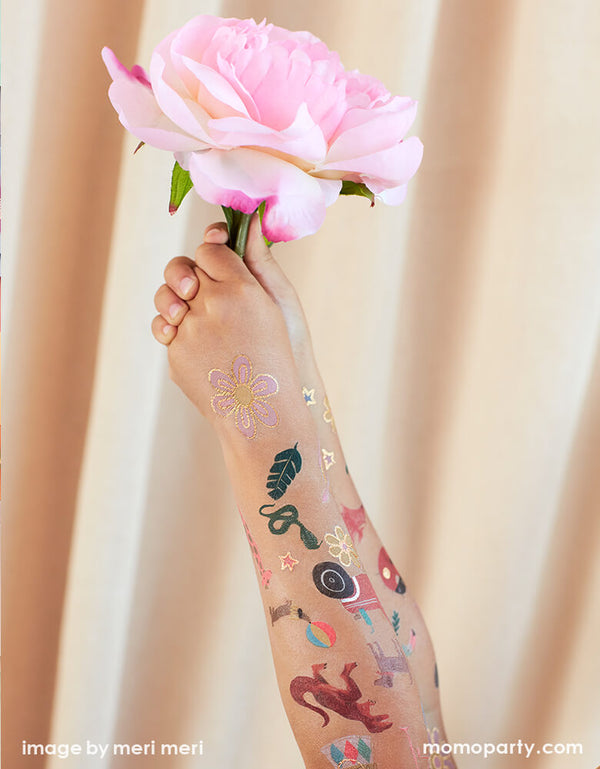 a kid holding a flower with full of fun bright colors with shimmering silver foil detail temporary Tattoos on her arms