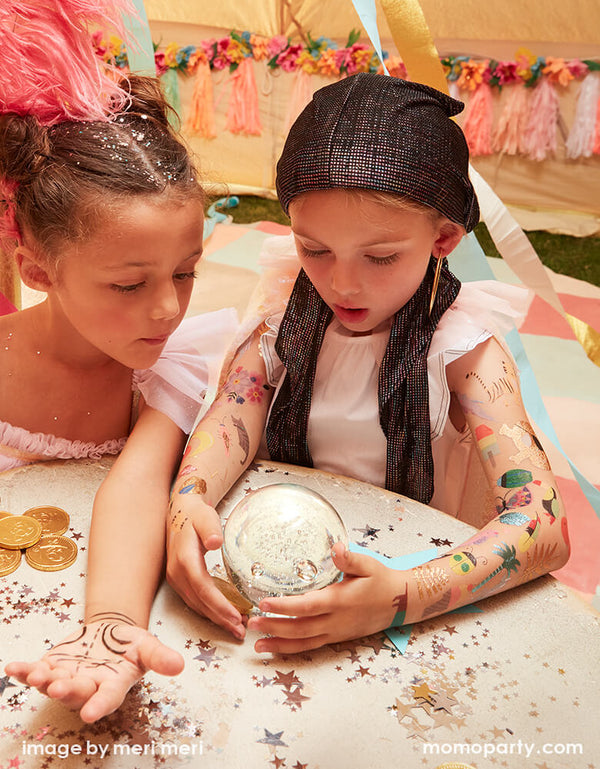 two girls dressed up like Gypsy Fortune Tellers, they watch a crystal ball  on a table, with full of cool bright colored and foil detailed temporary Tattoos on her arms