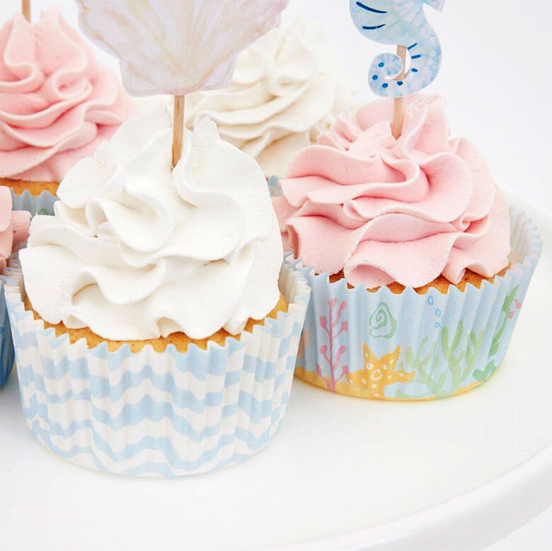 close up details of Pink and white cupcakes decorated with Meri Meri mermaid cupcake kit. With beautiful mermaids, a seahorse and seaweed toppers and pastel blue color cupcake cases.
