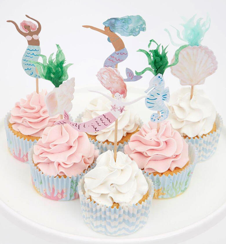 Pink and white cupcakes decorated with Meri Meri mermaid cupcake kit. With beautiful mermaids, a seahorse and seaweed toppers and pastel blue color cupcake cases.