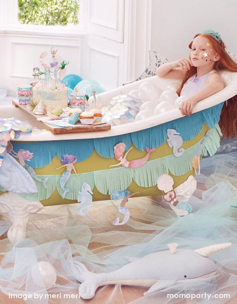 A Fun and gorgeous Mermaid Party at home. With a girl sitting inside bathtub, she dressed up like a mermaid, with lots of small latex balloons as bubbles. The bathtub decorated with Meri Meri Mermaid Fringe Garland, Light blue tulle fabric cover the ground as the ocean, There are Cake decorated with Mermaid Cake Toppers, morden Meri Meri Mermaid collection partywares all on the bathtub caddy tray. What a creative fun dreamy mermaid party for a girls birthday, a mermaid lover, or a under-the-sea party
