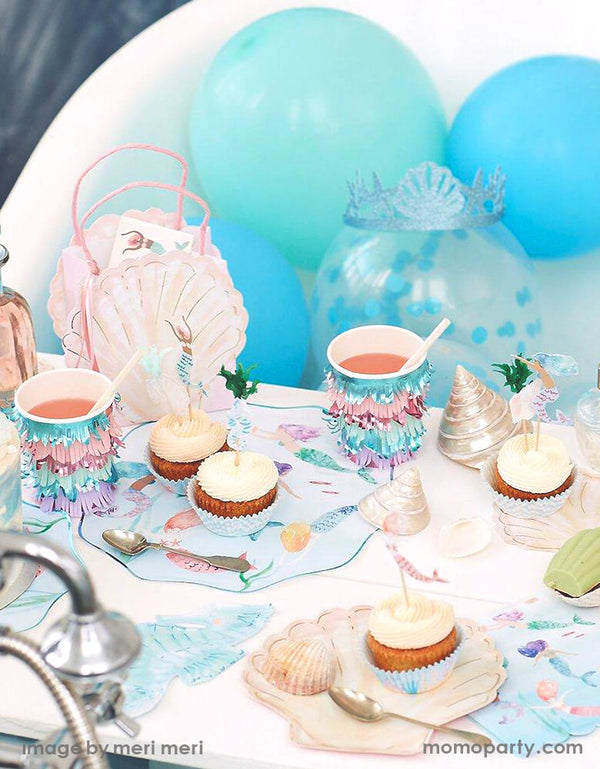 Detail look of a Modern Mermaid Party, There are Meri Meri Mermaid Swimming Plates, Watercolor Clam Shell Plates holding up cupcakes with Mermaid Cupcake topper, Seahorse Napkins, Mermaids Swimming Napkins, and Mermaid Scalloped Fringe Cups next to them, Mermaid seashell party bag with mermaid tattoo inside, sea shells as decorations. with Mixed blue,teal mint colored latex balloon behind it. What a fun dreamy mermaid party for eight kids birthday, or who love mermaid, or a under-the-sea party celebration