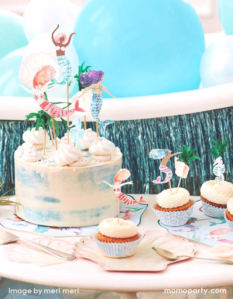 Detail look of a Modern Mermaid Party, There are Meri Meri Mermaid Swimming Plates, Watercolor Clam Shell Plates holding up cupcakes with Mermaid Cupcake toppers, Watercolor Seashell Napkins next to them, A naked cake decorated with Mermaid Cake Toppers. with Mixed blue,teal mint colored latex balloons and blue fringe garland behind it. What a fun dreamy mermaid party for eight kids birthday, or who love mermaid, or a under-the-sea party celebration