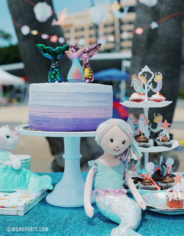 Mermaid beach party table set up with Pastel Ombre color Mermaid Tail Candle and reversible sequin fabric mermaid tail toppers on the cake, Jellycat Aqua-Lily Mermaid Doll, cupcakes