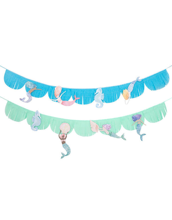 Meri Meri Mermaid Fringe Garland. 8.5 feet. This gorgeous fringed tissue paper garland, featuring beautiful mermaids and seahorses, with shimmering blue and pink foil detail. Beautifully crafted from tissue paper sewn onto satin ribbon with cotton thread, The mermaids are threaded onto metallic silver thread, Lots of shiny blue and pink foil detail for a special effect. modern and high quality partyware for a mermaid themed birthday, under-the-sea party, or a cute room decoration for mermaid lovers.