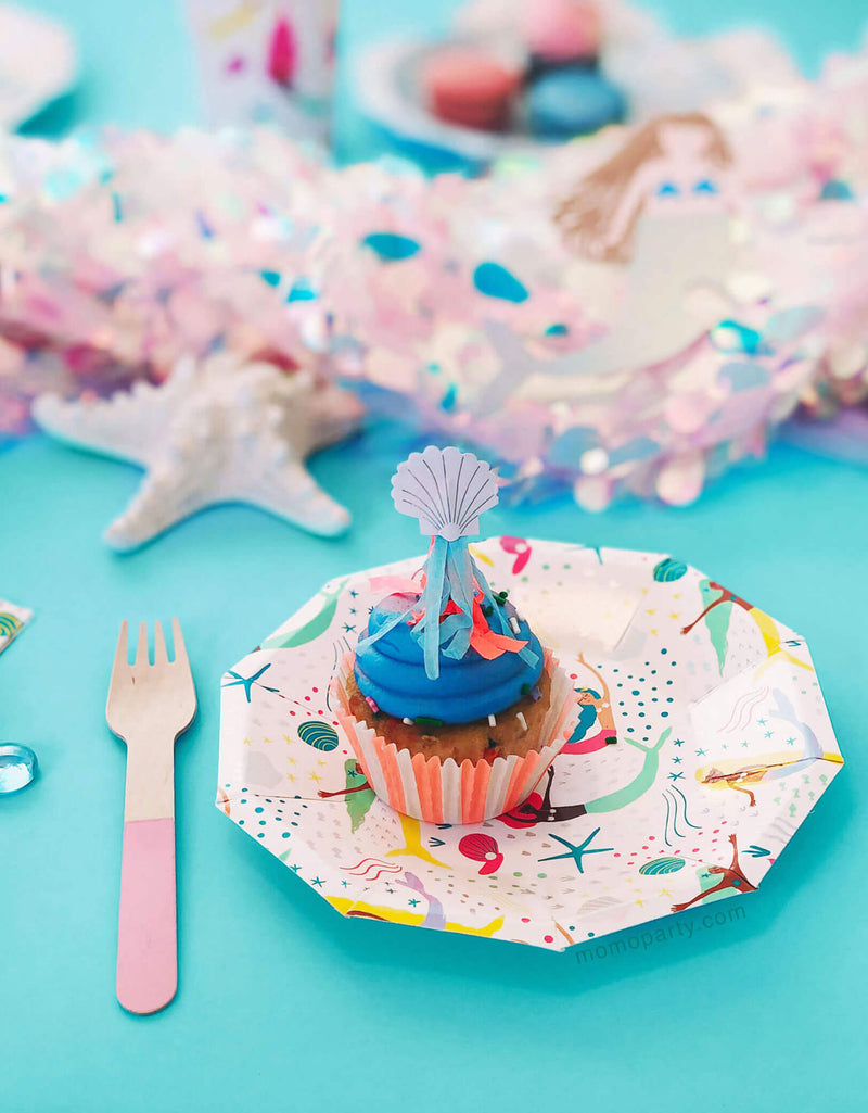 Close up shot of Mermaid Themed Party with under the sea mermaid paper Plates with jellyfish topper cupcake on top of it