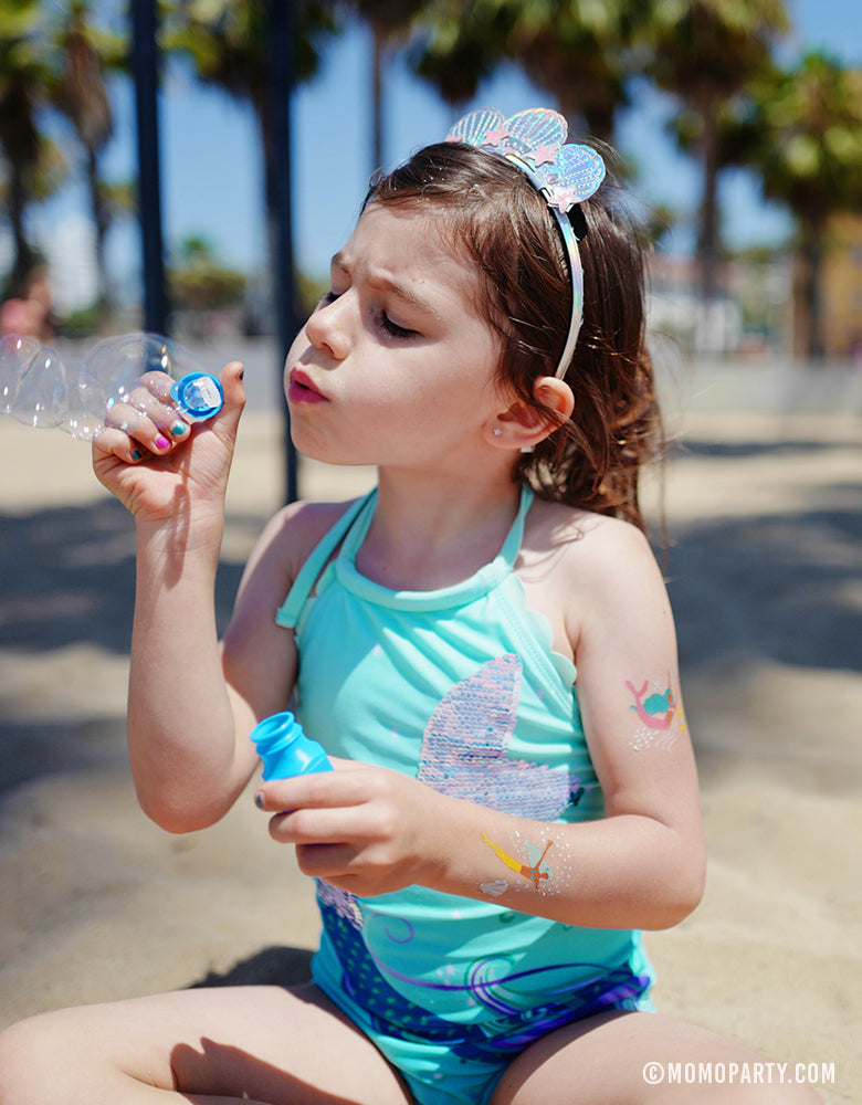 Girl siting on the beach and blowing bubbles with Daydream Society Under The Sea Mermaid Temporary Tattoo on her arm