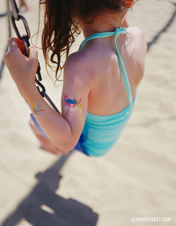 Girl swing on the beach with Daydream Society Under The Sea Mermaid Temporary Tattoo on her arm