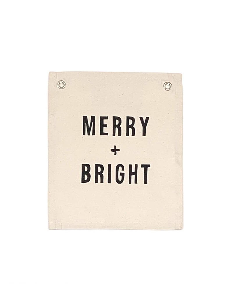 Imani Collective MERRY + BRIGHT BANNER. size 12in x 10in with 5/16 inch grommets. This modern hanging banner was sewn and screen printed by hand on natural canvas by local artisans in Kenya. It's a perfect Holiday decoration for your entrance hall or even your little one's playroom! Sold by Momo party store provided modern party supplies, boutique party supplies, chic holiday party supplies and high end party supplies