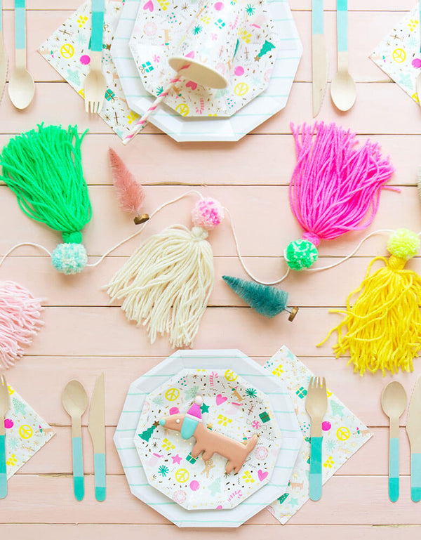 Daydream Society Merry and Bright Holiday Party Supplies on a pink table filled with festive colorful tassels and Christmas themed decorations
