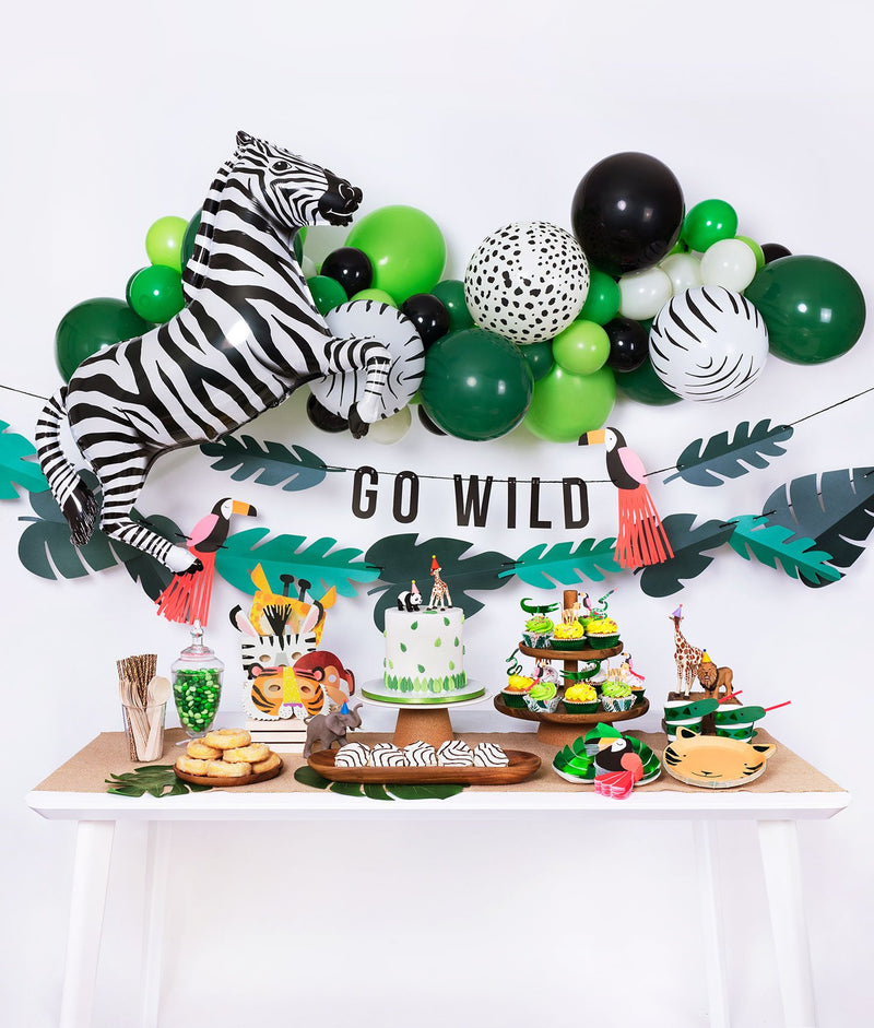 Momo Party jungle themed birthday party box with animal print balloon garland, zebra foil balloon, go wild garland decoration and tiger plates, tucan napkins, green foil plates, cake, cupcake, animal mask for kid's safari themed inspiration