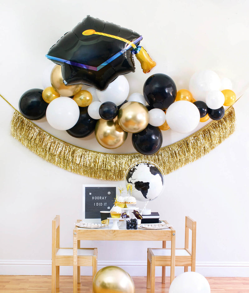 "Momo party modern graduation party at home box, come with black, gold and white Latex balloon garland, Black Graduation Cap Foil Balloon, Gold Tinsel Fringe Garland as backdrop decoration. Black and Gold stripe paper plates, stripe napkins, Assorted Gold Dipped Cups, b&w globe, letter board with ""hooray i did it"" sign, cupcakes, black gum balls on a kid table for a graduation celebration"