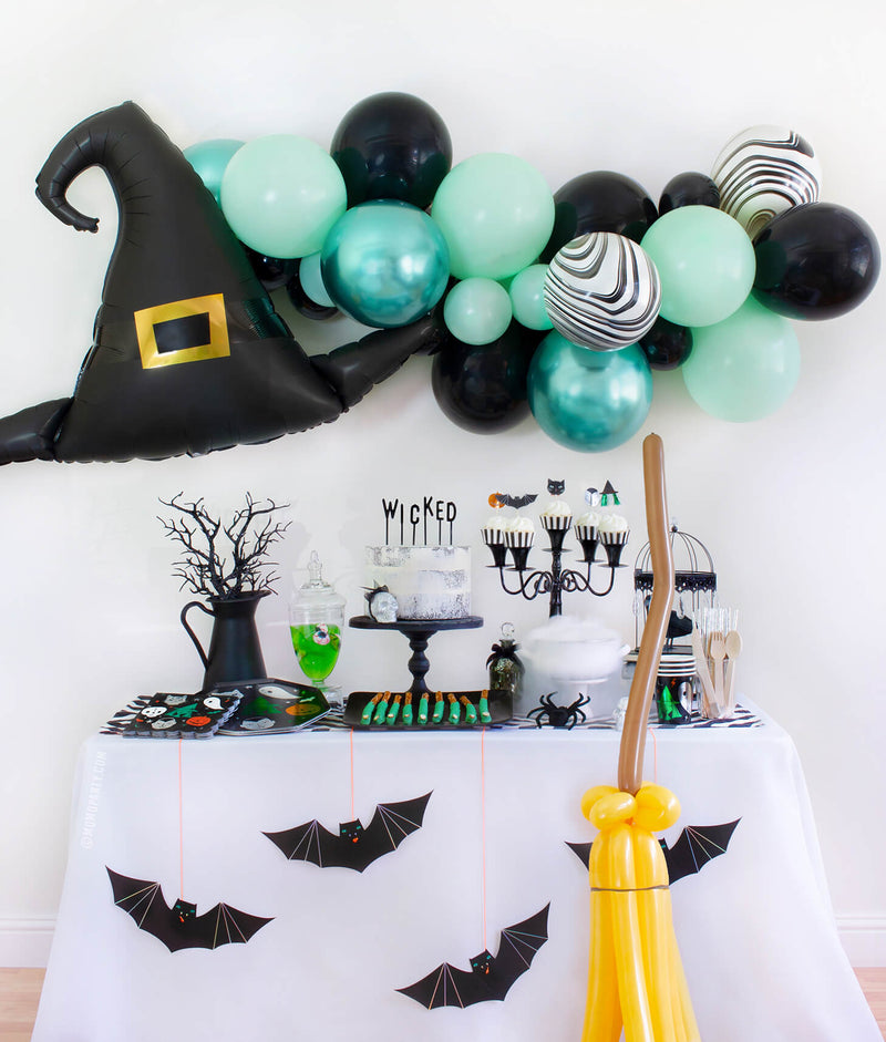 "Momo Party 2020 Witch Please themed Halloween Party at home inspiration look with Anagram Witch Hat Satin Foil Balloon and pastel Green toned Latex Balloon Garland for wall decoration. Meri Meri Halloween Motif Dinner Plates, napkins and cups, cake with letter board cake topper spelled of ""Wicked"", witch cauldron, Apple jelly with eyeball candy in a jar, witch fingers pretzels on the dessert table, Meri Meri Hanging Bats and balloon animal witch broomstick in front of the table"