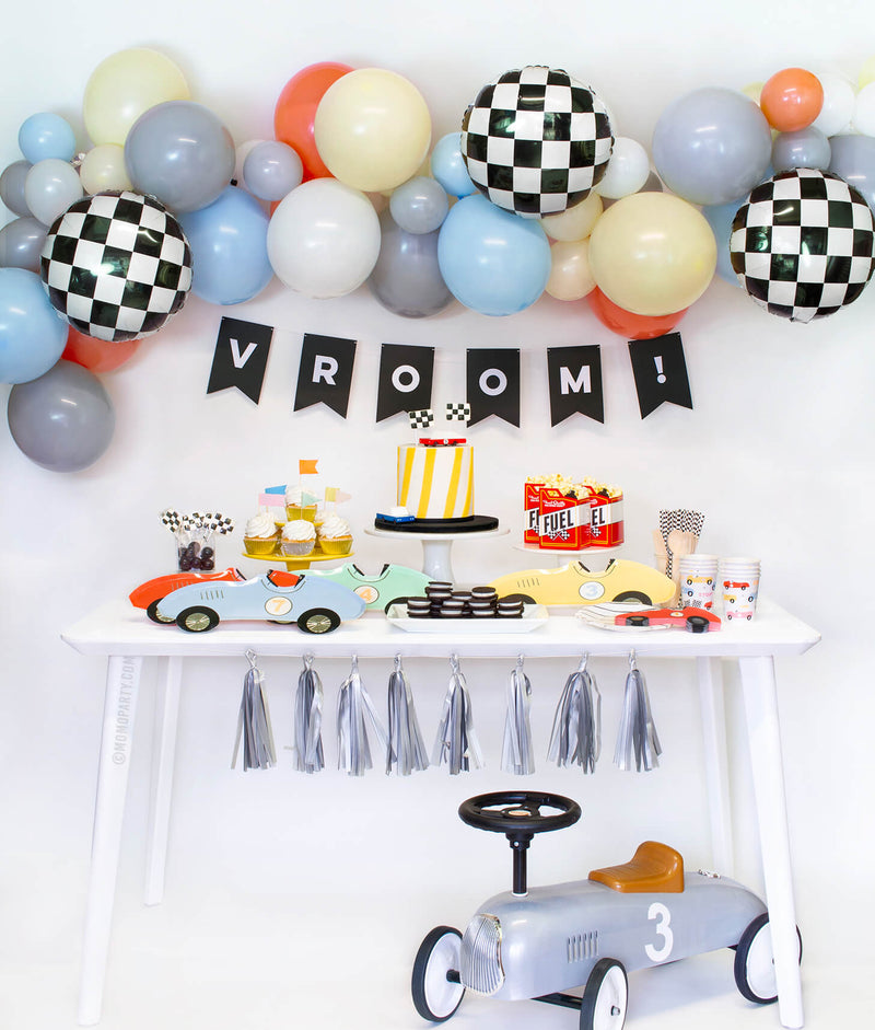 Momo Party Race Car Box, set up inspiration with Meri Meri race car paper plates, race car shape napkins, race car graphic party paper cups, black strip small plate, neon confetti flag cupcake kit, candy car as cake topper, Fuel treat favor box with popcorns as tableware, colorful balloon cloud, black costume letter banner with script of Vroom!,  checkerboard foil balloon as decorations for modern Race car, car themed birthday party