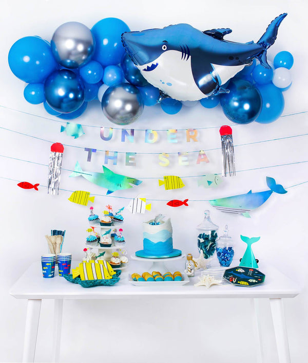 Momo Party Box of under the sea shark themed birthday party idea with balloon garland, shark foil balloon, Under the sea garland as decoration and fish graphic paper cups, fish die-cut napkins, shark party hats, plates and cupcakes as table set up