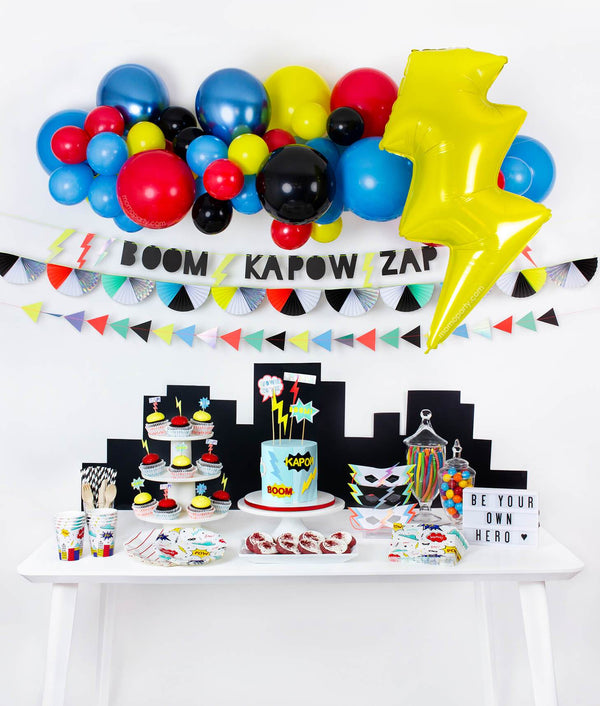modern boy and girl superhero themed birthday party idea with balloon garland, Lightning Bolt Foil balloon, Super hero Slogan Garland and tablewares