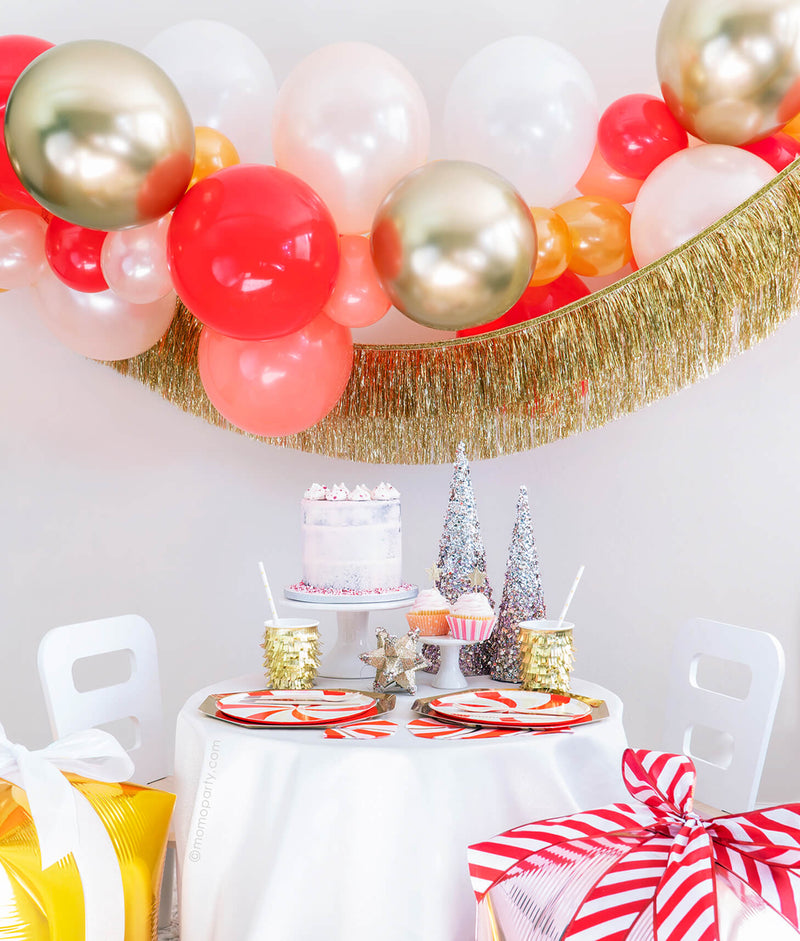 Momo Party Holiday party box - Christmas Candy Cane Glam Holiday Box, Featuring Meri Meri Gold Large Dinner Plates, Peppermint Swirl Side Plates, Gold Fringe Party Cups, Candy Cane Napkins, Silver Wooden Cutlery Set, Gold Star Party Straws, Gold Tinsel Fringe Garland, Candy-cane-glam themed Gold, Red, Pearl White, Coral, Pearl peach latex balloon garland. decorated with your cake, cupcakes, sparking trees for a modern classic cute christmas holiday celebration