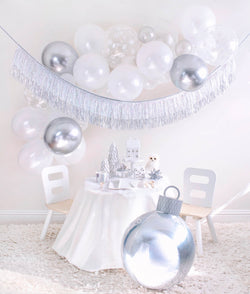 Momo Party 2020 Holiday White Christmas Holiday Box, Small party set up with White Scalloped Large Plates, Silver Sparkle Reindeer Plate, Silver Sparkle Tumbler Cup, Gleaming Large Napkin, Silver Wooden Cutlery and white trees, white house decor on the cake stand, Owl and silver star ornaments on the table, Silver Ornament Foil Balloon in the front. White, silver, snowflake mixed latex balloons cloud, and Silver Tinsel Fringe Garland as wall decoration for a simply modern gorgeous white Xmas party