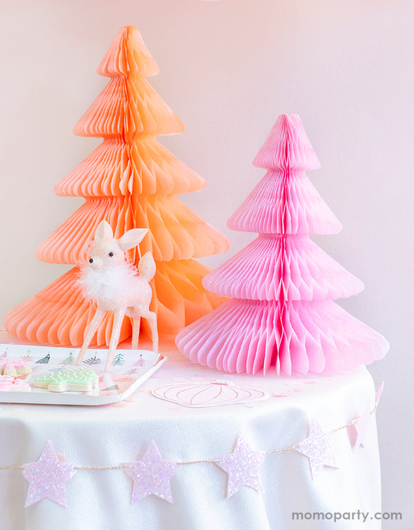 Pastel Pink Christmas party table set up with Devra Party Peach and light pink Honeycomb Paper Christmas Trees, a cute deer ornament decoration, Fa la la christmas tree plate with tree cookies on a kid table, and StudioPep Pink Glitter Star Banner on the side of the table for a cozy celebration
