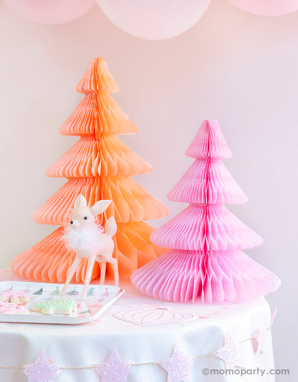 Pastel Pink Christmas party table set up with Devra Party Peach and light pink Honeycomb Paper Christmas Trees, a cute deer ornament decoration, Fa la la christmas tree plate with tree cookies on a kid table, and pastel matt pink balloons as decoration